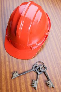 work helmet and keys on the table of a office
