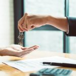estate agent giving house keys to man and sign agreement in office with vintage filter